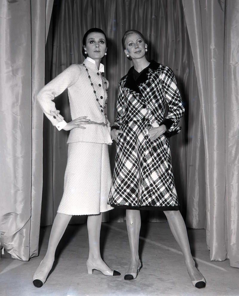 Paris, France, 21st July 1970, Models display a beige tweed skirt suit (left) and plaid grey coat (right) by French designer Coco Chanel being modelled in Paris (Photo by Popperfoto/Getty Images)